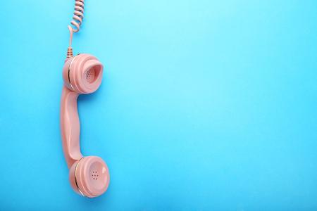 Pink telephone handset on blue background