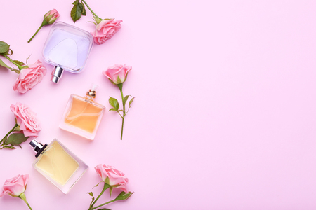 Perfume bottles with flowers on pink background