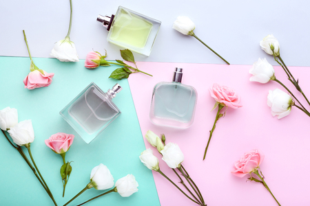Perfume bottles with flowers on colorful background Standard-Bild