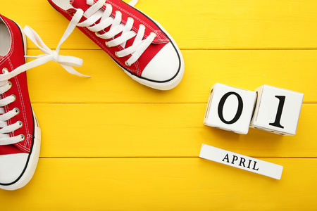 Calendar cubes with red sport shoes on yellow wooden table Archivio Fotografico
