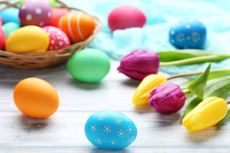 Colorful easter eggs with tulips on wooden table
