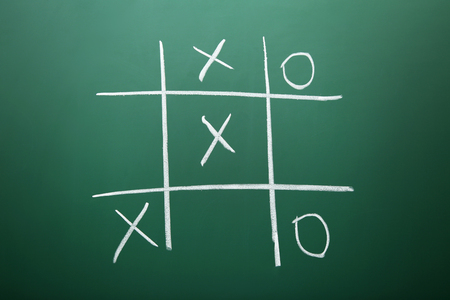 Tic tac toe game drawn by chalk on green school blackboard Reklamní fotografie - 97402726