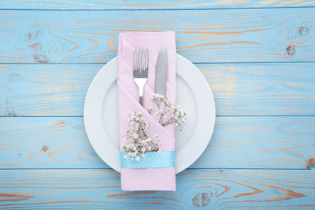Kitchen cutlery with plate and gypsophila flowers on blue wooden table 写真素材