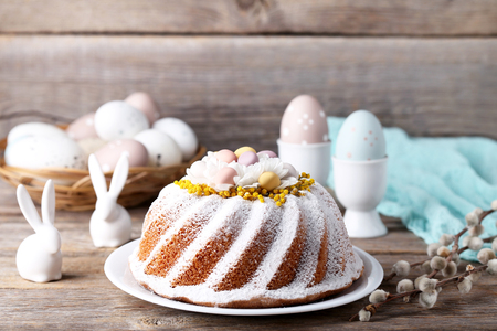 Easter cake with eggs and ceramic rabbits on grey wooden table