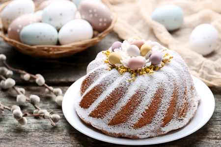 Easter cake with eggs and tree branches on wooden table