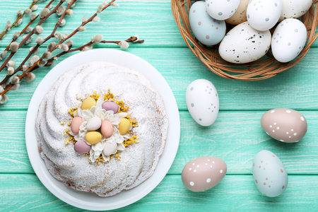Easter cake with eggs and tree branches on mint wooden table