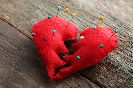 Broken red heart with needles on grey wooden table