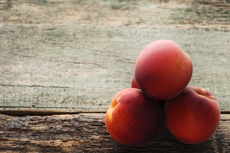 Sweet nectarines fruit on wooden table Фото со стока