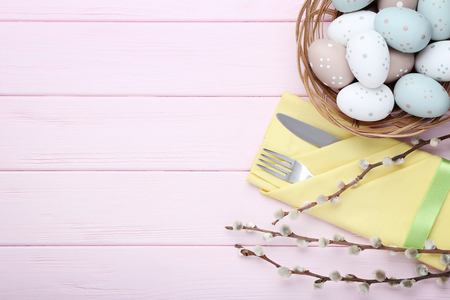 Kitchen cutlery with easter eggs and tree branches on pink wooden table Stock Photo