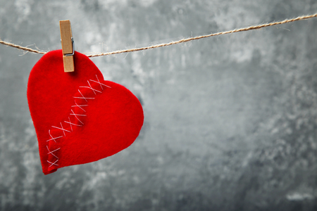 Broken red heart hanging on rope on grey background