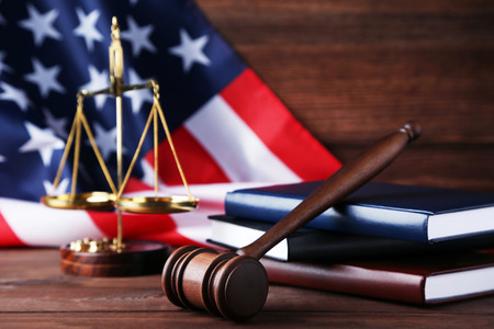 Judge gavel with scales, books and american flag on wooden table Banque d'images