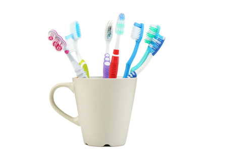 Toothbrushes in cup isolated on white background
