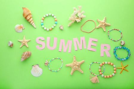 Inscription Summer with seashells on green background Stock Photo