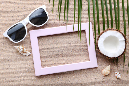 Wooden frame with seashells and green palm leafs on beach sand