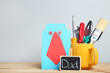 Fathers day concept and cup with tools on grey background