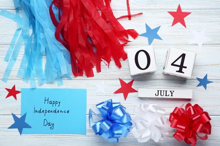 Cube calendar, pom poms and paper with inscription Happy Independence Day on wooden table