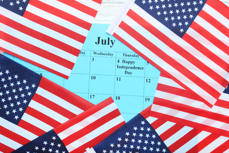 American flags with paper july calendar