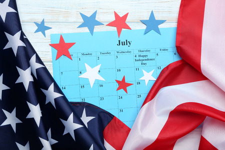 American flag with paper stars and July calendar on wooden table