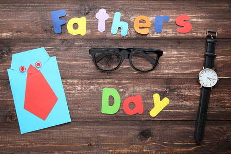 Inscription Fathers Day with glasses and paper shirt on wooden table