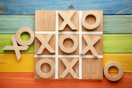 Wooden tic tac toe game on colourful table Banco de Imagens