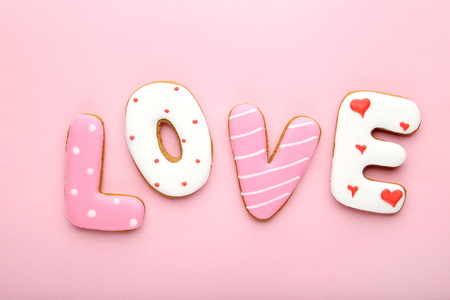 Inscription Love by homemade cookies on pink background