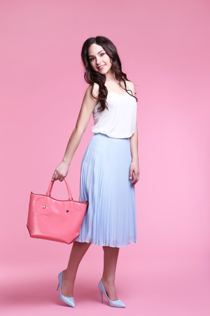 Beautiful young woman with handbag on pink background