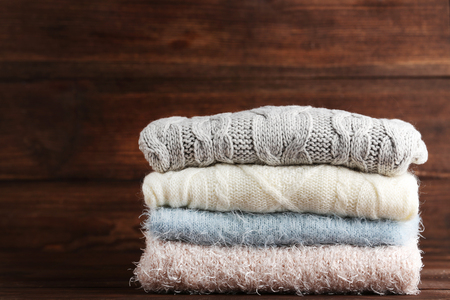 Stack of knitted sweaters on wooden table