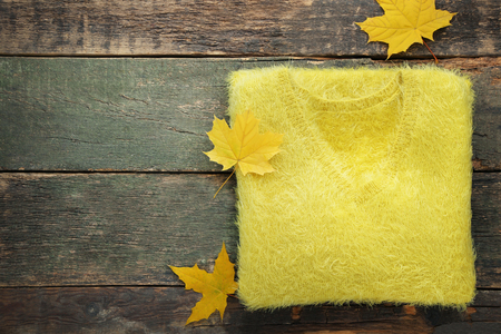Knitted yellow sweater with autumn leafs on wooden table