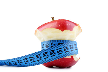 Red apple with measuring tape on white background Фото со стока