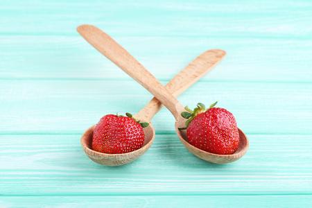Fresh strawberries in spoon on mint wooden table Standard-Bild - 103526822