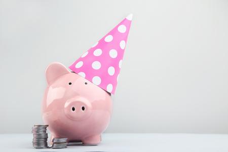 Hucha rosa con gorro de cumpleaños y monedas sobre fondo gris Foto de archivo - 104034230