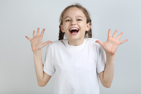 Surprised young girl on grey background Stok Fotoğraf - 104525777