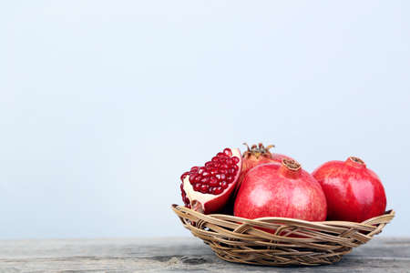Ripe and juicy pomegranate in basket on grey wooden table Stockfoto