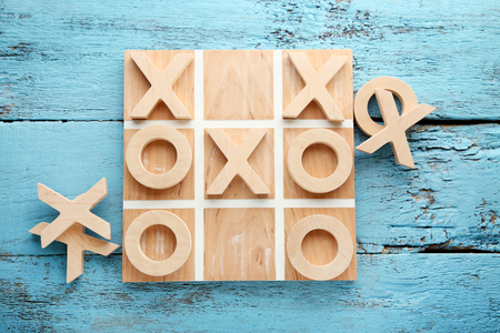 Wooden tic tac toe game on blue table Stock Photo