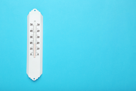 White thermometer on blue background
