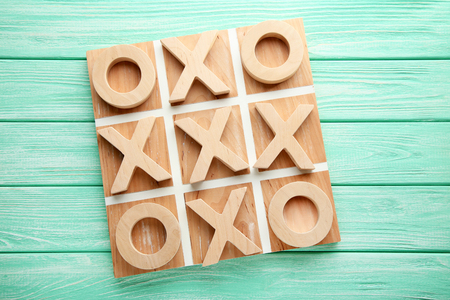 Wooden tic tac toe game on mint table