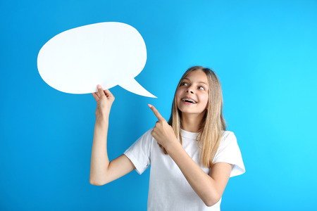 Young girl holding speech bubble on blue background Stockfoto