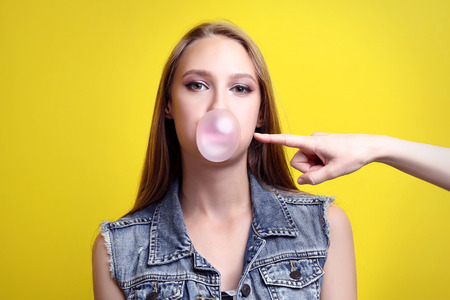 Young woman blowing bubble by chewing gum on yellow background