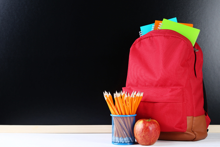 Red backpack with school supplies on black background 免版税图像