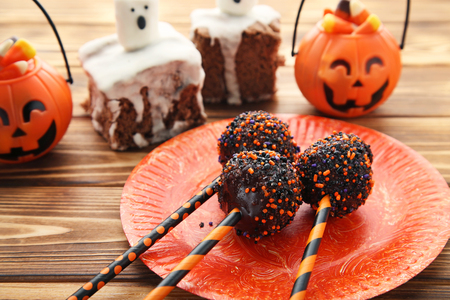 Sweet halloween cake pops on brown wooden table Stock Photo