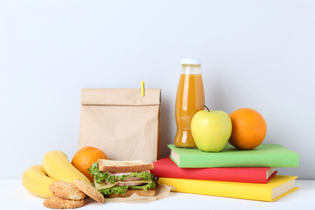 School lunch with paper bag and books on grey background