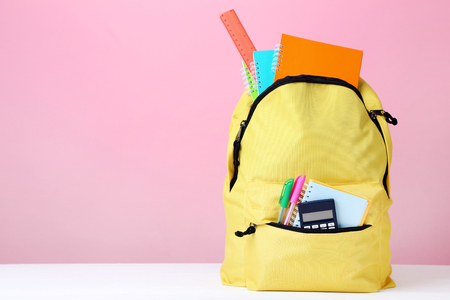 Yellow backpack with school supplies on pink background
