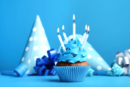 Cupcake with candles, blowers and paper caps on blue background Stock Photo