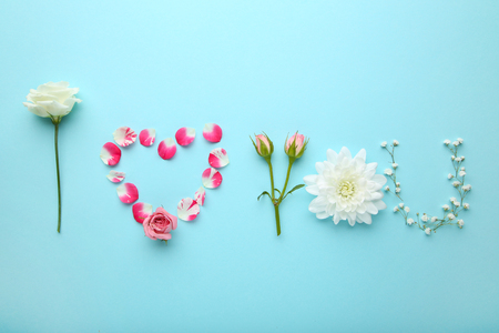 Inscription I Love You by flowers on blue background Stock Photo