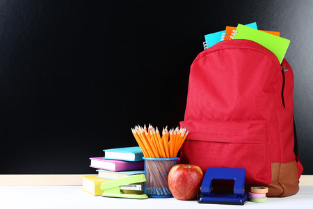 Red backpack with school supplies on black background Stock Photo