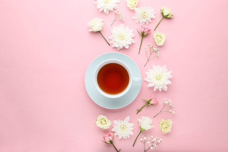 Flowers with cup of tea on pink background