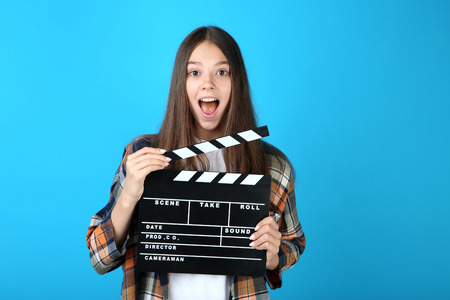Young girl with clapper board on blue background Banque d'images