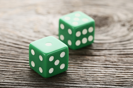 Green dice on grey wooden table