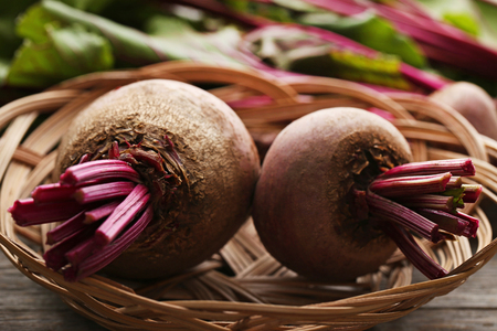 Fresh and ripe beets in basket on wooden table Banco de Imagens