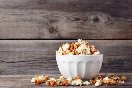 Caramel popcorn in bowl on wooden table